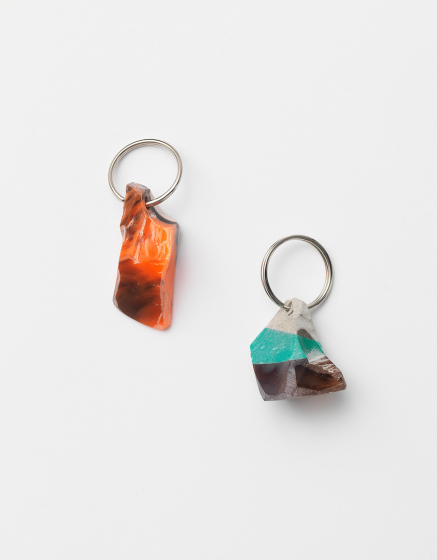 Two small brightly colored mineral or rock like objects with a keychain ring in each one