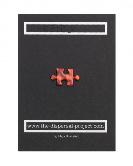 A picture-puzzle piece made of photo mounting board has been sewn with red thread onto the center of a piece of black cardboard