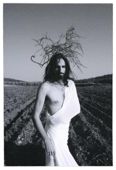 Photo: In the foreground, a man with long dark hair is standing in front of a fallow field with deep furrows and is wrapped tightly in a white cloth that leaves half his torso exposed. On his head, some foliage reminiscent of the crown of thorns.