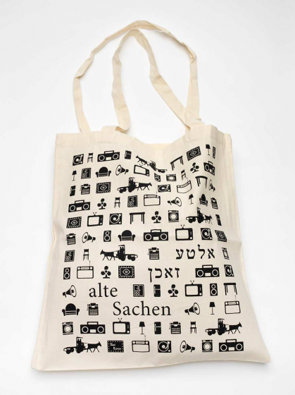 """Canvas bag covered in pictograms of furniture, boom boxes, megaphones, horse-drawn carriages, and the label """"alte Sachen,"""" meaning """"old things,"""" in German and Yiddish"""