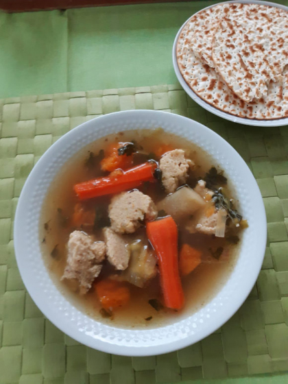A plate of chicken soup, carrots and matzah balls stands on a green background. On another plate lies bread.