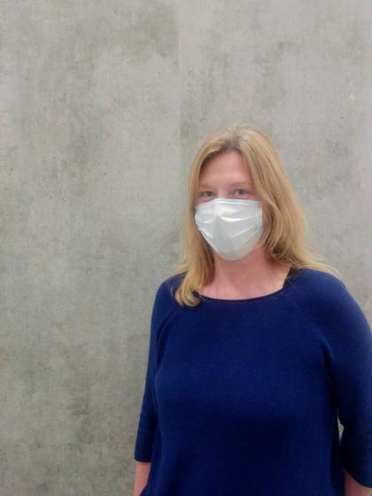 Porträt von Iris Saeger mit Atemschutzmaske vor Betonwand