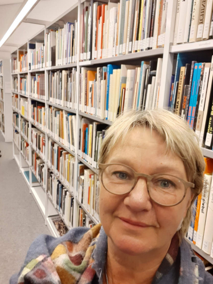 Selfie by Ulrike Sonnemann in front of a bookshelf in the library