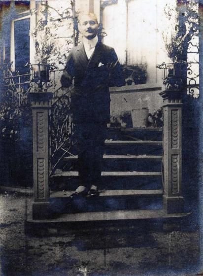 Junger Mann auf einer Treppe vor einem Haus. Er schaut verschmitzt und hat beide Arme angewinkelt, es lässt sich nicht genau erkennen, ob er die Hände in die Jackentaschen gesteckt hat.