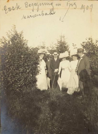 """Drei Herren in Anzug mit Hut und Stock und drei Damen in weißen Kleidern mit großen Hüten und Sonnenschirmen auf einer Lichtung. Oben auf dem Foto steht in Handschrift: """"Erste Begegnung m Fritz Marienbad 1909"""", ein Pfeil weist auf Fritz."""