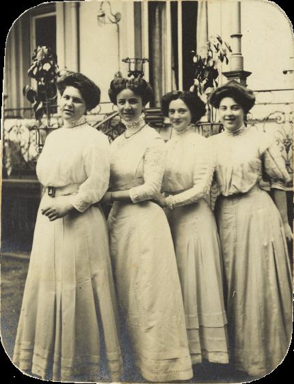 Schwarz-Weiß-Foto, das vier in einer Reihe schräg hintereinander stehende junge Damen im Dreiviertelprofil vor einem Haus zeigt. Alle tragen weiße, hochgeschlossene Kleider und Hochsteckfrisuren.