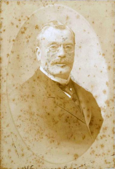 Stockfleckiges Porträtfoto eines gesetzten Herren im Anzug. Er trägt eine Krawattennadel, Schnurrbart und Monokel und wirkt sehr distinguiert.