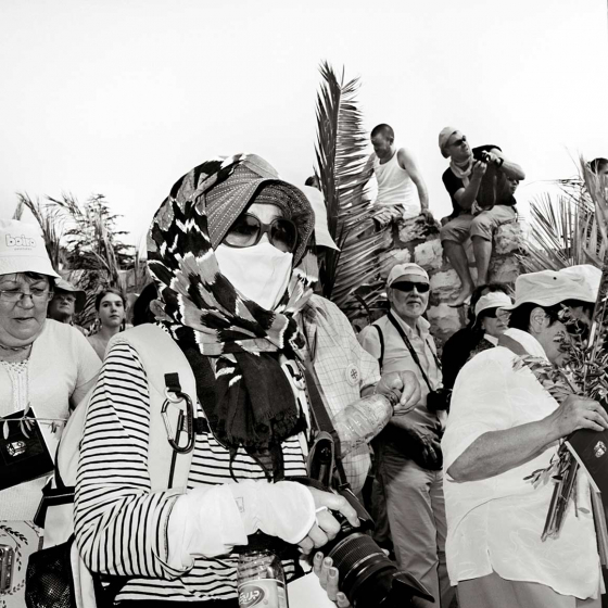Black-and-white-photo of a procession with palm branches, in the foreground a woman with camera, hat, headscarf, sunglasses and mouthguard
