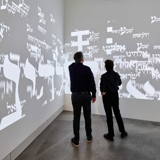 People watching a video projection of Hebrew letters on the walls of a room
