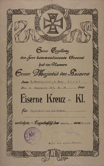 A certificate from 1914 decorated with a patterned border, the Iron Cross is on the top of the page