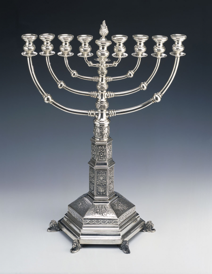 Richly decorated silver Hanukkah menorah, at the foot six lions