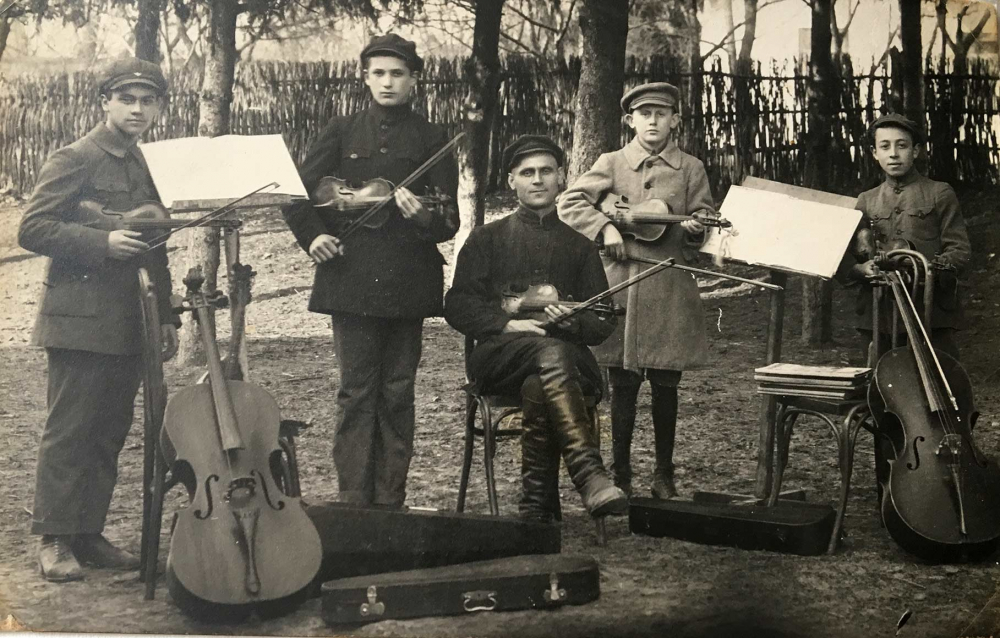 Black-and-white photograph of five young musicians with string instruments and music stands, outdoors