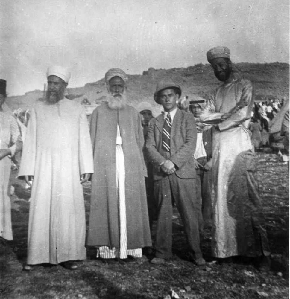 Black-and-white photo of four men in a desert landscape: one in a suit, tie, and hat; the other three with long beards and robes