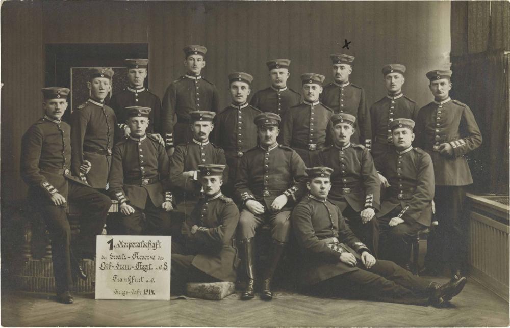 Schwarz-weiß-Foto: 17 uniformierte Soldaten, stehend oder sitzend, Atelieraufnahme