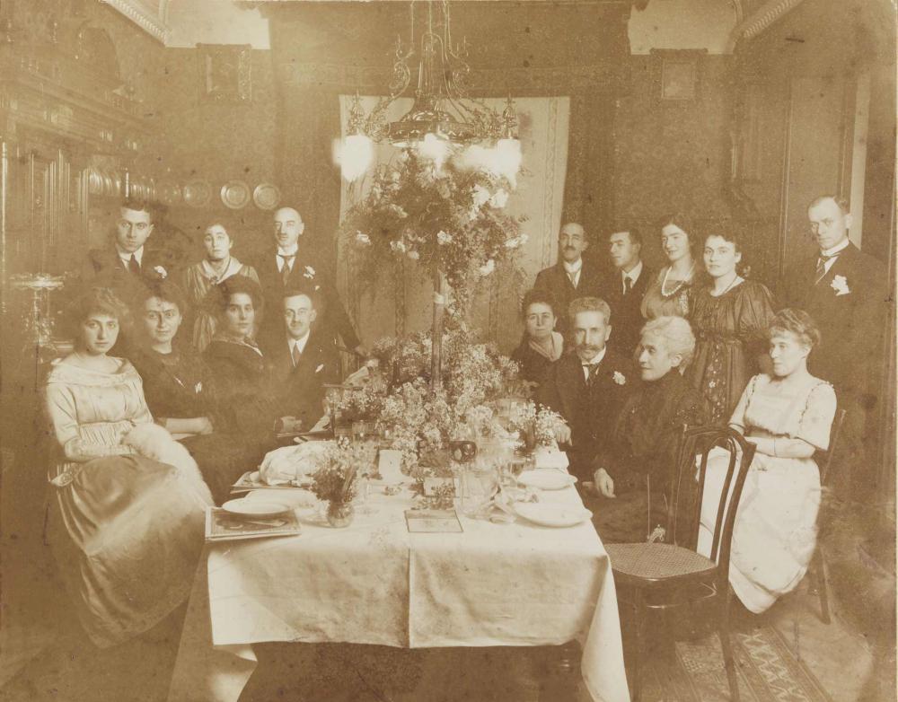 Schwarz-weiß-Foto: Festgesellschaft, in einer bürgerlichen Wohnung um einen gedeckten Tisch versammelt