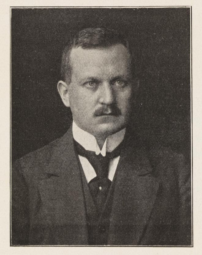 Black-and-white photograph: Man with moustache wearing a suit