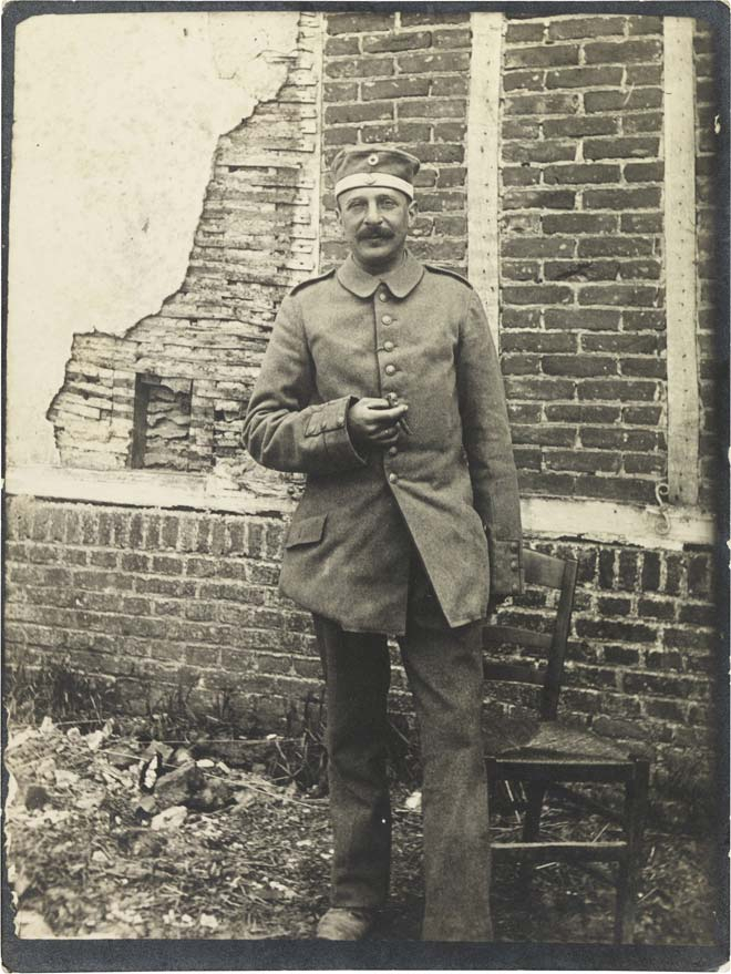 Black-and-white photograph: A soldier in uniform smoking in front of a building with cracked stucco