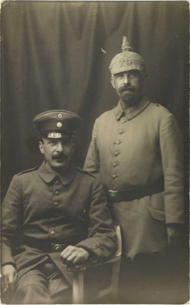Black-and-white photograph: Two soldiers in uniform, one sitting, one standing, studio portrait