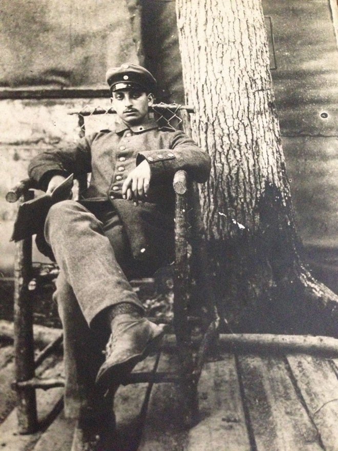lack-and-white photograph: Soldier in uniform sitting in a chair with a tree trunk in the background