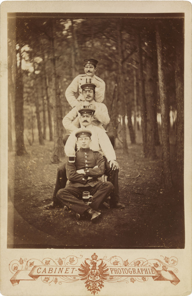 Schwarz-weiß-Foto: Vier uniformierte Soldaten mit Biergläsern, in einem Waldstück