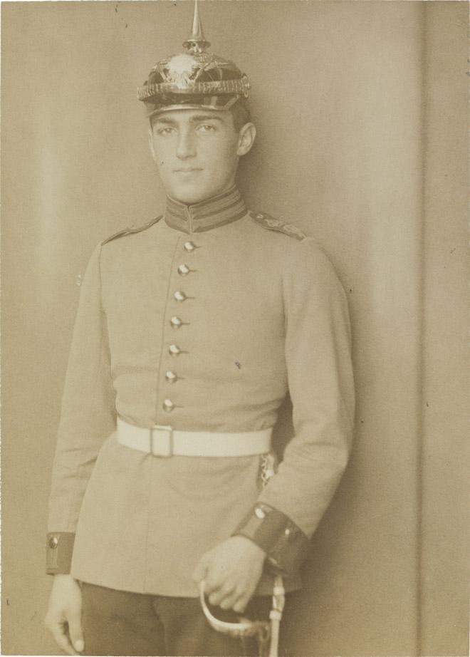 Schwarz-weiß-Foto: Junger Mann in Soldatenuniform mit weißem Gürtel, Pickelhaube und Degen, Atelieraufnahme