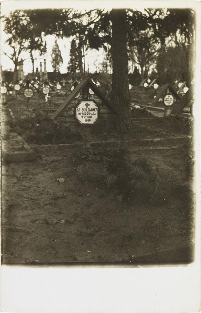 Schwarz-weiß-Foto: Grab mit Kreuz und Inschriftstafel, weitere Gräber im Hintergrund