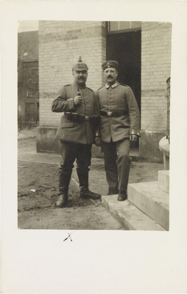 Schwarz-weiß-Foto: Zwei uniformierte Soldaten mit Pickelhaube bzw. Militärmütze, vor einem Gebäude stehend