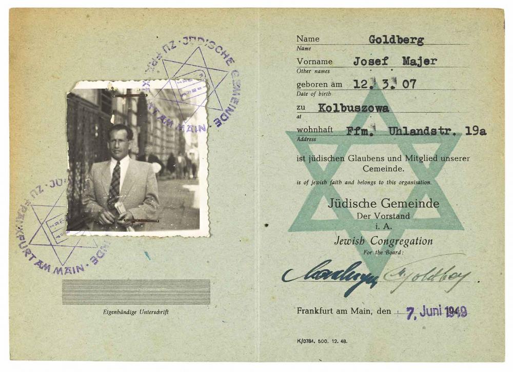 Mitgliedsausweis, das Foto zeigt Oberkörper und Kopf eines Mannes, im Hintergrund eine Straße und Häuser
