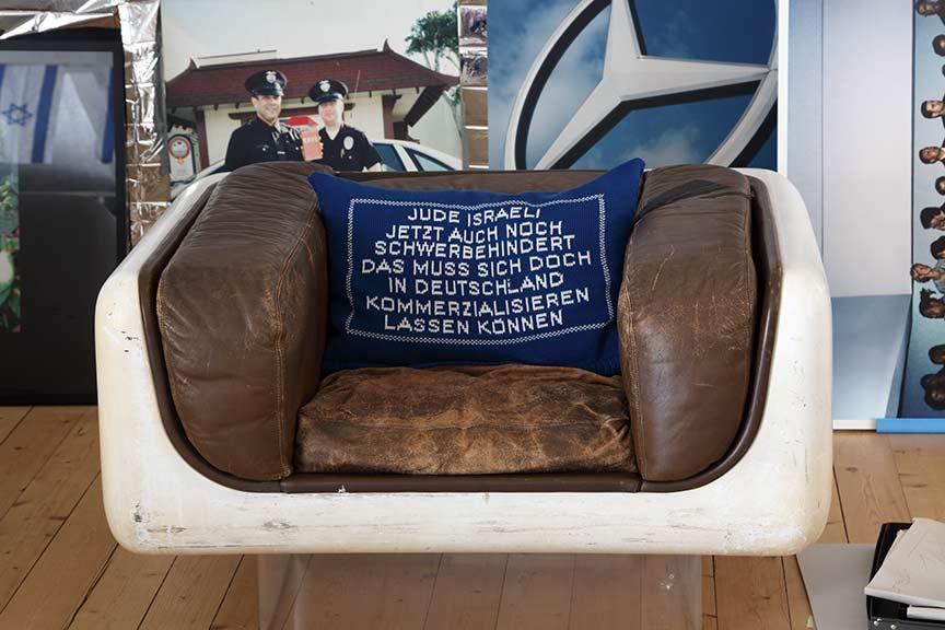 Blaues Kissen mit gleichmäßigerer, weißer Aufschrift in einem abgewetzten braunen Ledersessel