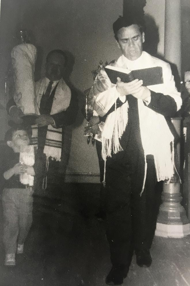 Black-and-white photo of a man standing, wearing a tallit and holding an open book