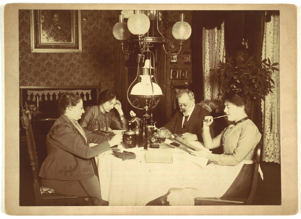 Vier Personen am Wohnzimmertisch in einer Aufnahme um 1900