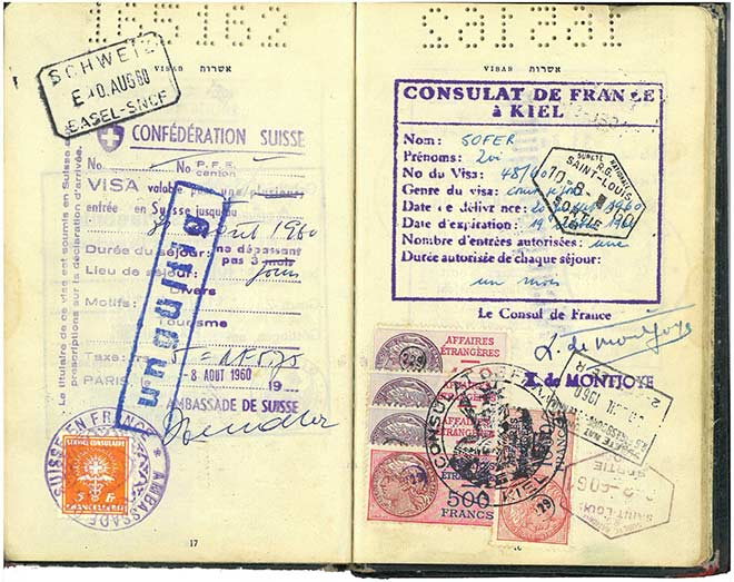 """Open passport with a variety of colorful stamps, including one from the """"Consulat de France à Kiel"""""""