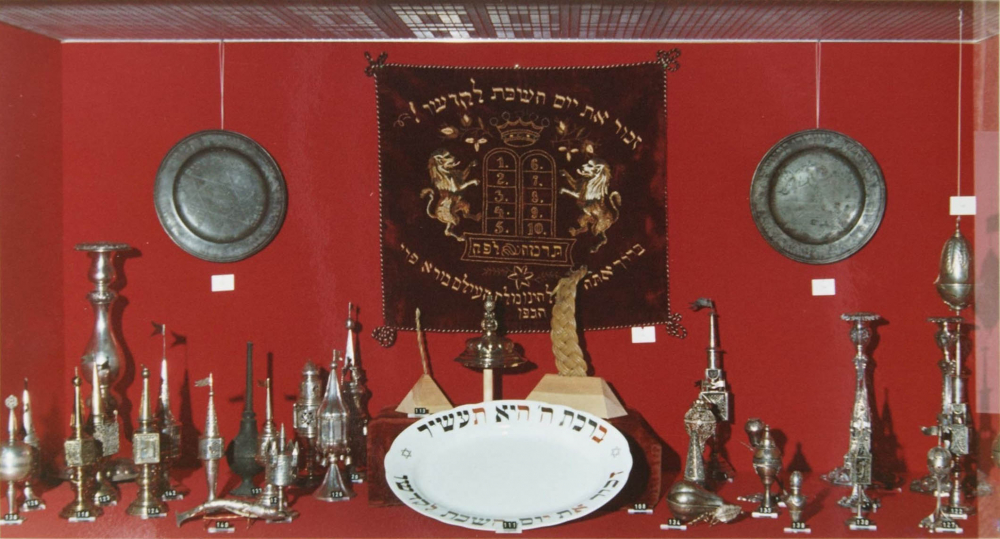 Photo of an exhibition showcase with Judaica objects against a red background