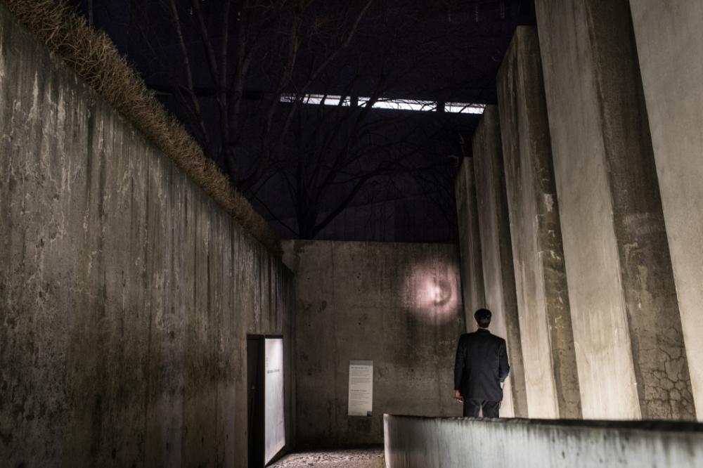 Ein Mitarbeiter der Sicherheit beleuchtet mit einer Taschenlampe den Garten des Exils im Jüdischen Museum Berlin.