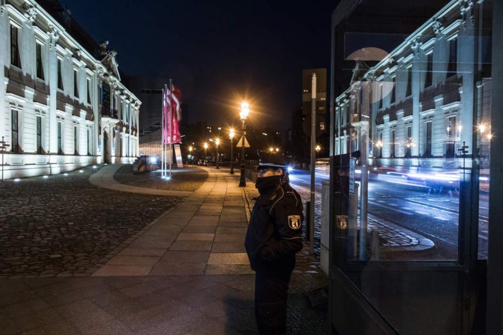 Eine Polizistin bewacht nachts den Haupteingang des Jüdischen Museums Berlin