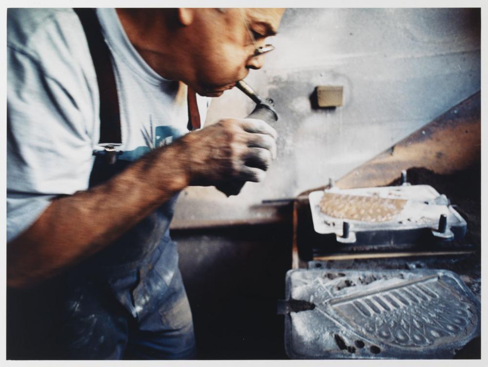 Herr Ehrlich sprüht feinen Wassernebel auf die Sandform der Chanukka-Lampe