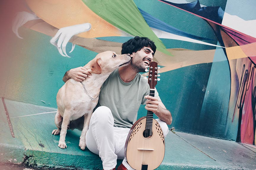 Ein lachender Mann mit Hund und Mandoline sitzt vor einer bunt bemalten Häuserwand