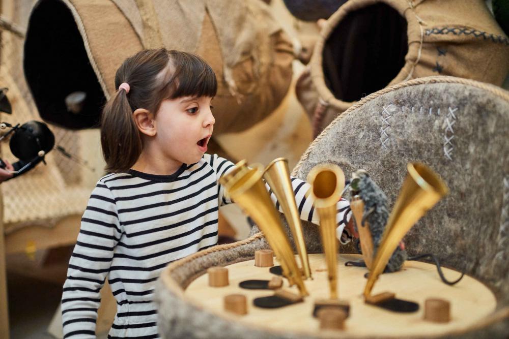 Kind mit gestreiften Pullover steht vor Trichtern, die auf einem Holzelemt stehen und hat den Mund geöffnet