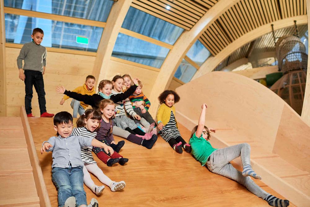 11 Kinder rutschen eine breite Holzrutsche runter