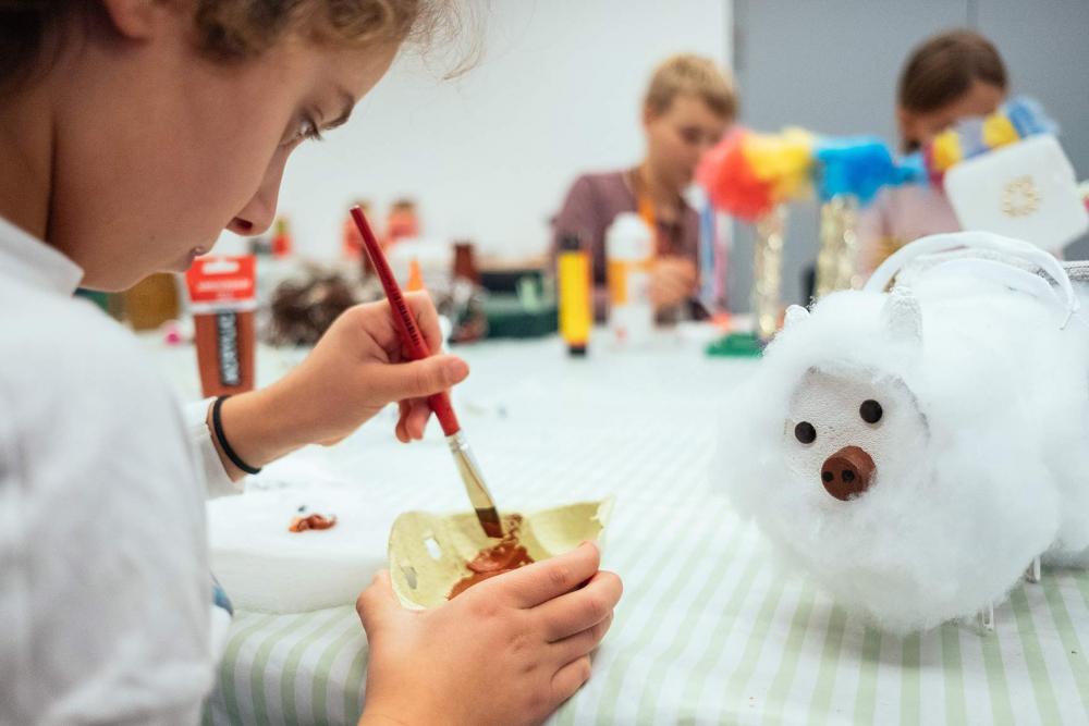 Ein Kind bepinselt ein Stück Pappe, auf dem Tisch vor ihm steht ein gebasteltes Schaf
