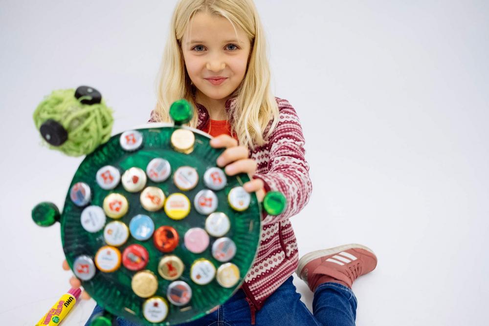 Ein Kind hält ein gebasteltes Modell einer Schildkröte in die Kamera