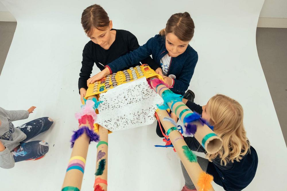 Drei Kinder halten einen großen, gebastelten Gegenstand