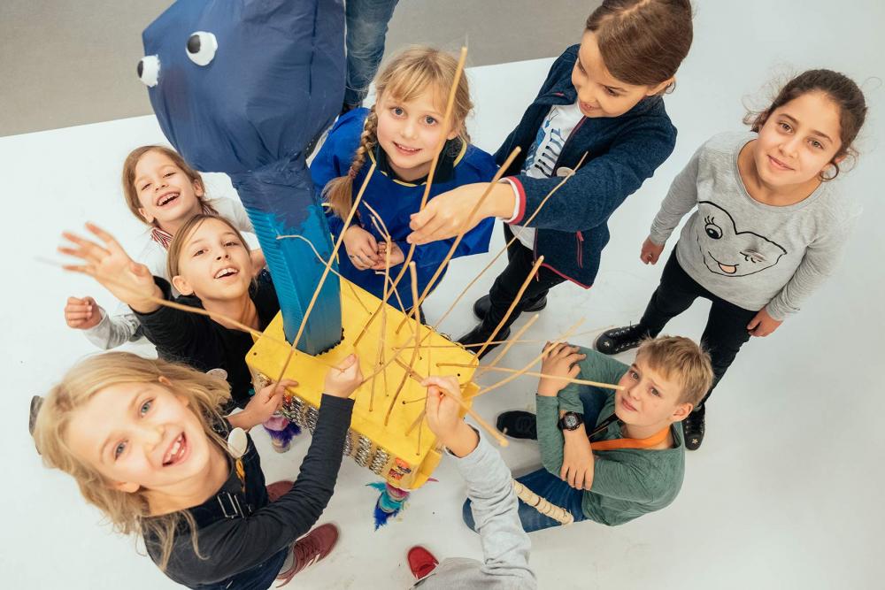 Kinder posieren lachend um einen gebastelten Gegenstand