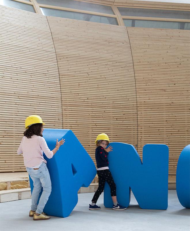 Kinder mit Bauhelmen spielen mit großen Buchstaben des Schriftzugs ANOHA