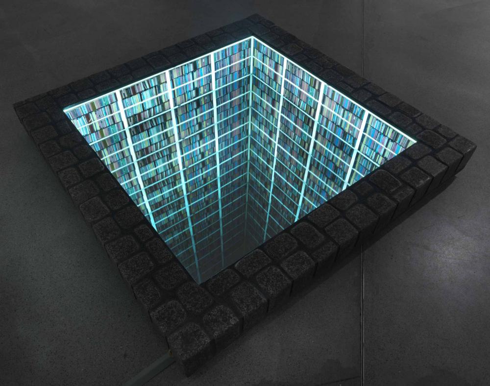Blick von oben in eine im Boden versenkte Bibliothek mit quadratischem Grundriss; die Regalwände leuchten grünblau.