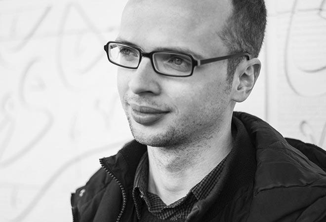 Schwarz-Weiß-Porträt eines jungen Mannes mit Brille im Halbprofil