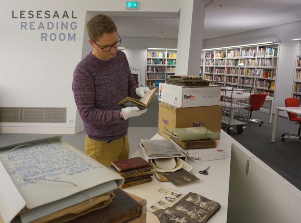 Halbausgepackte Kiste in einer Bibliothek, auf den Tisch im Vordergrund liegen Schwarz-Weiß-Fotos und weitere Dokumente, ein Archivmitarbeiter liest in einem der ausgepackten Alben