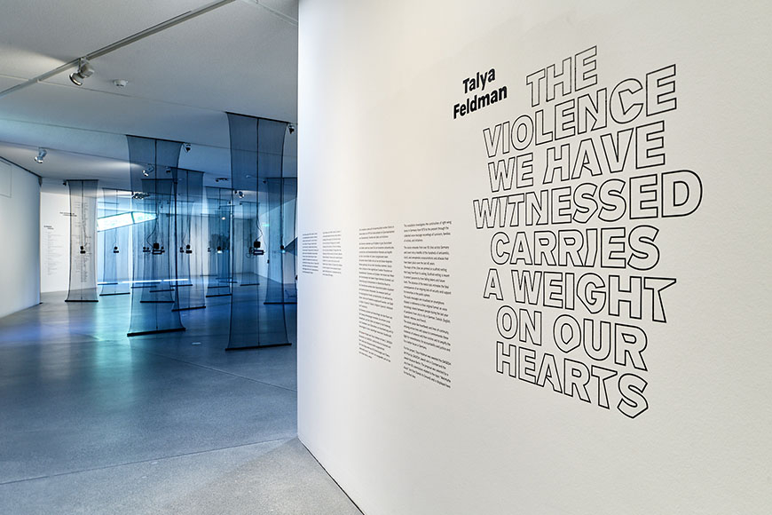 Room view of the exhibition, in the foreground a wall with text