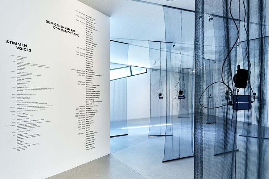 Room view of the exhibition, in the foreground black transparent fabric panels and a wall with text