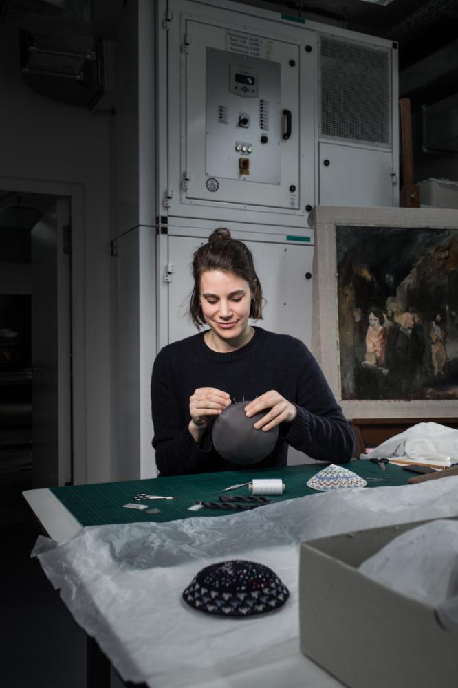 Eine junge Frau sitzt an einem Arbeitstisch in einem Atelier und bestickt Kippas.